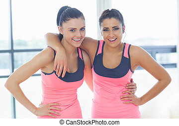 Two fit young women smiling in a bright exercise room