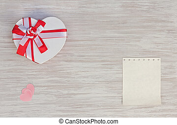 Valentine`s Day gift, heart and paper on wooden background.