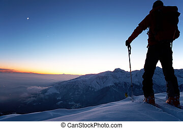 Exploration - At dusk a brave backcountry skier reaching the...