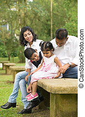 indian family sitting in the park lifestyle photo