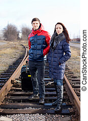 Impatient young couple waiting on the train tracks
