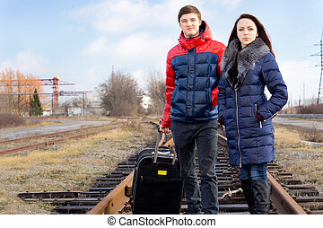 Young couple with a case waiting for the train