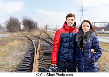 Young couple waiting on the railway tracks with a suitcase...