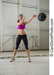 Medicine ball work out - Young brunette woman exercising...