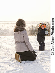 Small boy throwing a snowball at his mother - Small boy...