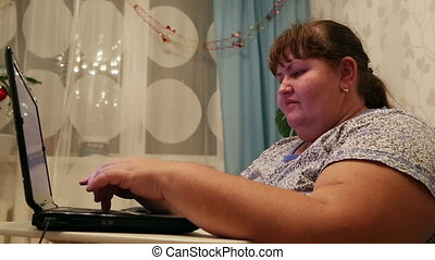 overweight woman typing on computer at home