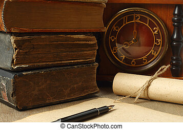 Retro composition with books, clock, paper and pen on wooden...