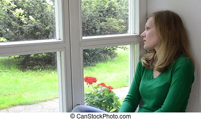 sad woman window sill - sad worried woman sits on window...