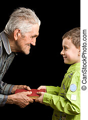 Grandson and grandfather - Grandfather giving a book to his...