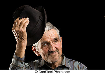 Old man saluting with his hat, isolated on black