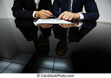 Negotiating - Image of human hands during reading contract