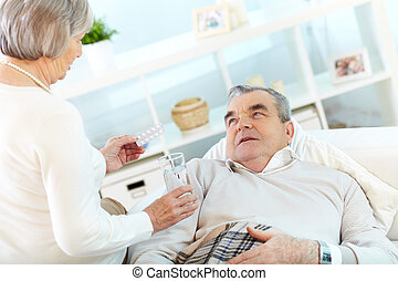 First aid - Portrait of mature woman giving tablets and...