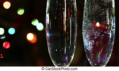 glasses with champagne and candle against festive lights background