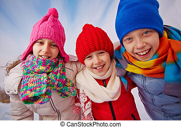 Happy friends - Joyful kids in winterwear looking at camera...