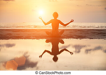 Yoga woman sitting in lotus pose on the beach during sunset, with reflection in water in bright colors.