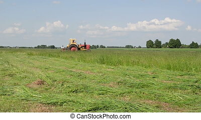 grass fine line - tractor travels through the meadow leaving...