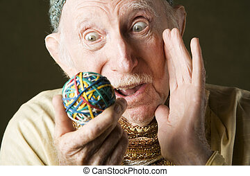 Man contemplating a rubber band ball - Senior man in knit...