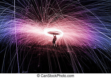 Showers of hot glowing sparks from spinning steel wool