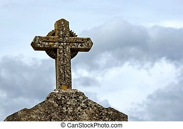 Stone cross on gravestone against blue cloudy sky at a...