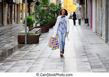 Portrait of a beautiful woman with shopping bags walking...