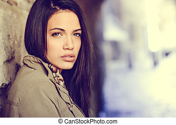 Young woman with green eyes in urban background - Portrait...