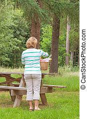Rear view of a Woman preparing a picnic