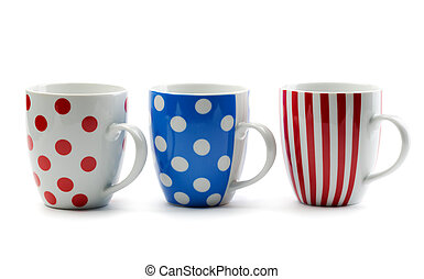 Three porcelain cup in colored stripes and dots. Isolate on...