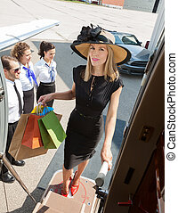 Full length portrait of confident rich woman carrying...