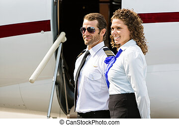 Airhostess And Pilot Looking Away Against Private Jet -...