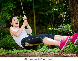 Swinging on seesaw - Young woman swinging on seesaw outdoor...