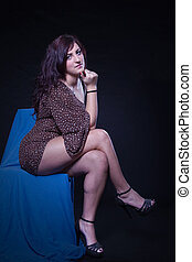 Young woman in sexy dotted mini dress sitting on a blue...