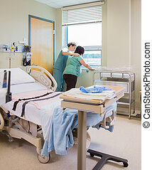 Nurse Comforting Pregnant Woman At Window In Hospital Room