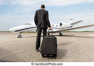 Businessman Walking Towards Corporate Jet - Rear view of...
