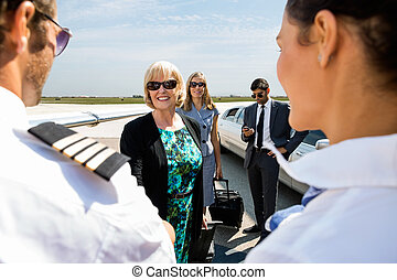 Business Colleagues Greeting Airhostess And Pilot At...