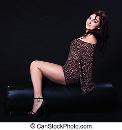 Young woman in sexy dotted mini dress sitting on a punching...