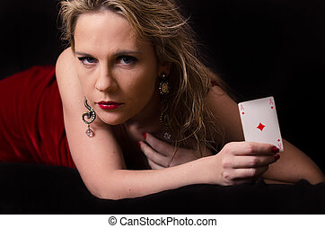 Woman in red with playing card on black background