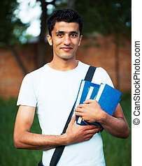 Arab male student with books outdoors looking very happy