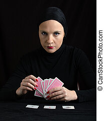 Woman in black with playing cards on black background