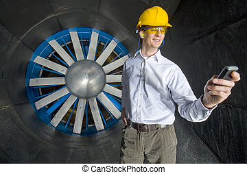 A smiling engineer, looking at his phone