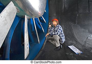 Inspecting a windtunnel - An engineer, wearing a checkered...