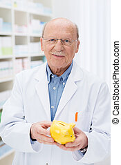 Successful pharmacist holding a piggy bank - Successful...