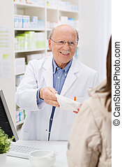 Friendly pharmacist dispensing medicine - Friendly elderly...