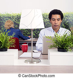 Flexible working space - people working behind laptops in a...