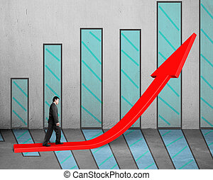 Businessman walking on growing red arrow with chart