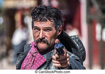 Serious Armed Cowboy - a cowboy pointing a gun at the camera