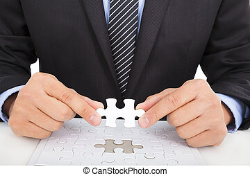 businessman holding a jigsaw