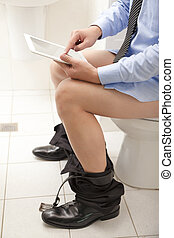 man using a tablet PC while sitting on the toilet