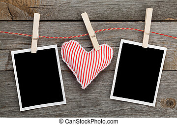Two blank instant photos and red heart hanging On wooden...