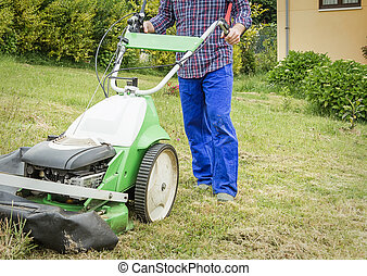 Young man mowing the lawn with a lawnmower machine