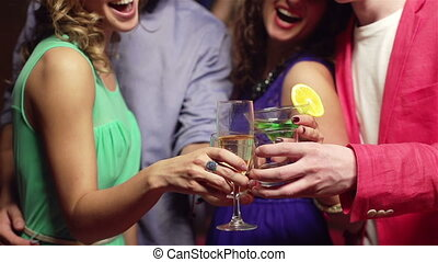 Cheers! - Happy young people clinking their glasses and...